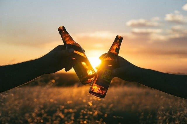 Beer bottles with sun between them.