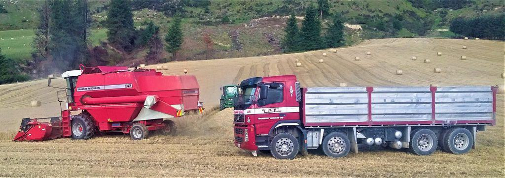 The transport truck waits near the combine harvester to receive its next load of grain.