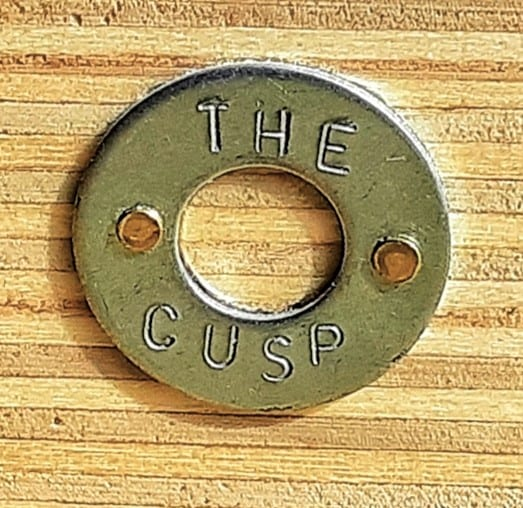 Close up of The Cusp's logo: a washer engraved with The Cusp.
