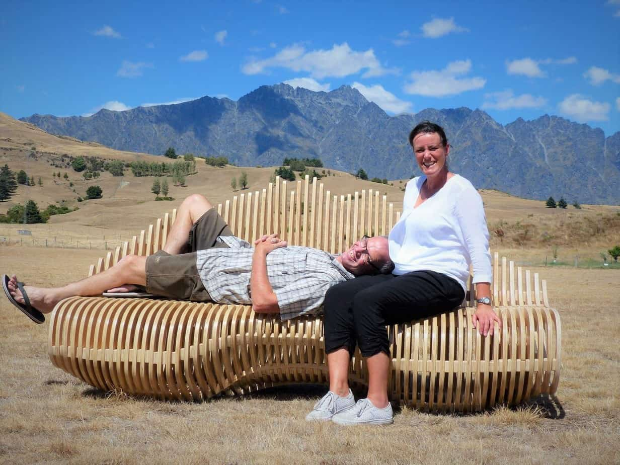 Kim Patterson and Stephen Counsell on the seat with the Remarkables Mountain Range in the background.