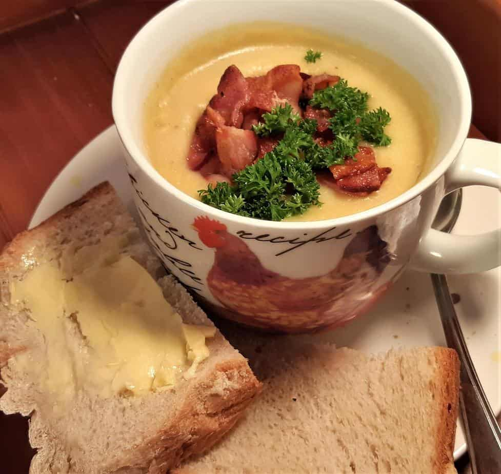 Bowl of soup with a slice of bread fresh from the bread maker.