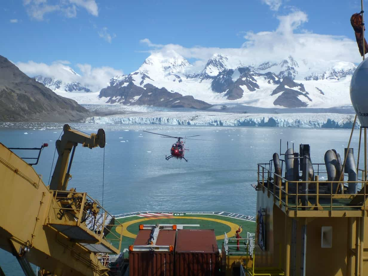 Helicopter flying into land on a ship's helipad at South Georgia Island. Glaciers and mountains in the background.