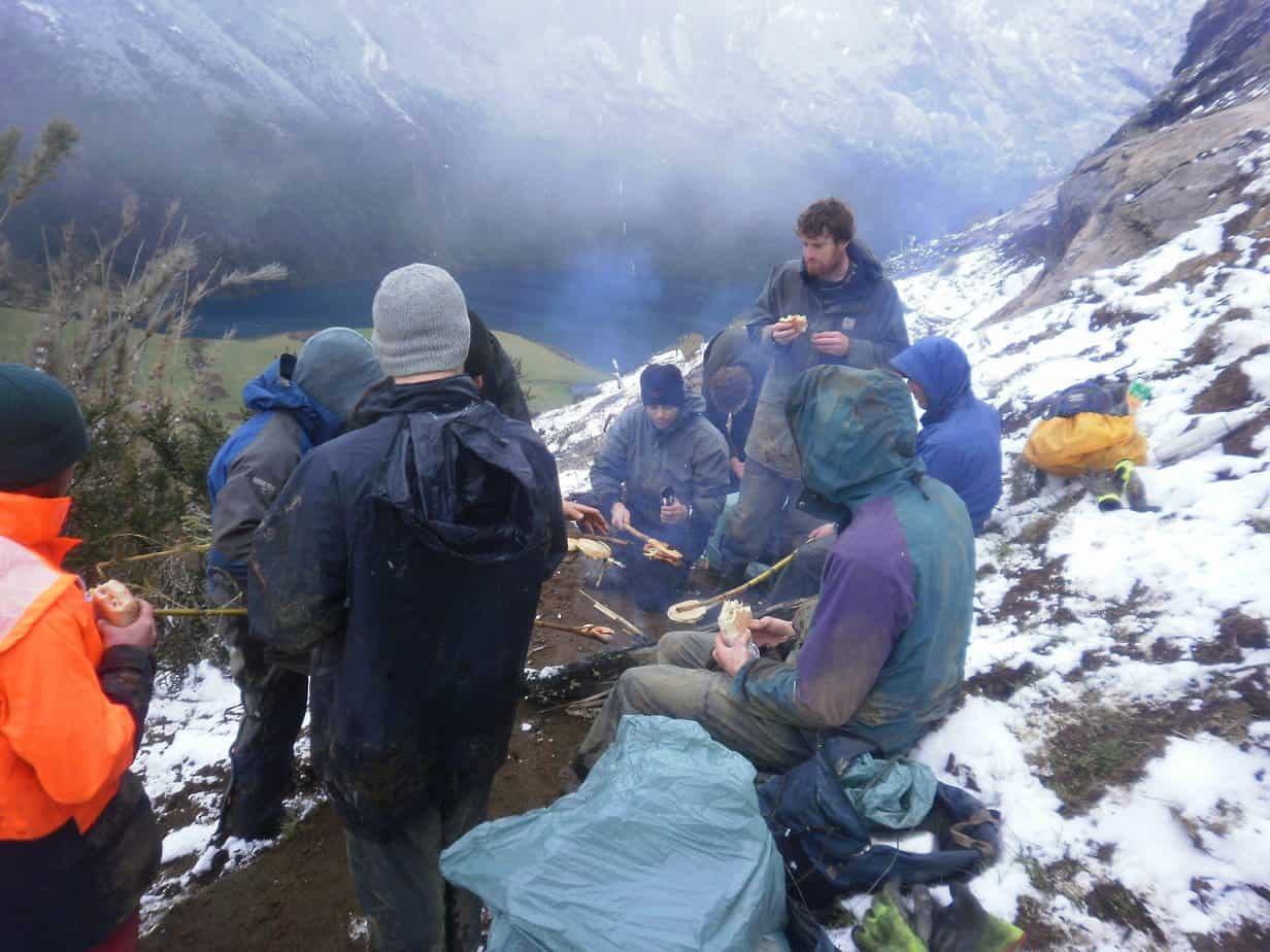 Trail-builders on the cycle track in the Chilean mountains, cooking dried bread to make it more palatable.