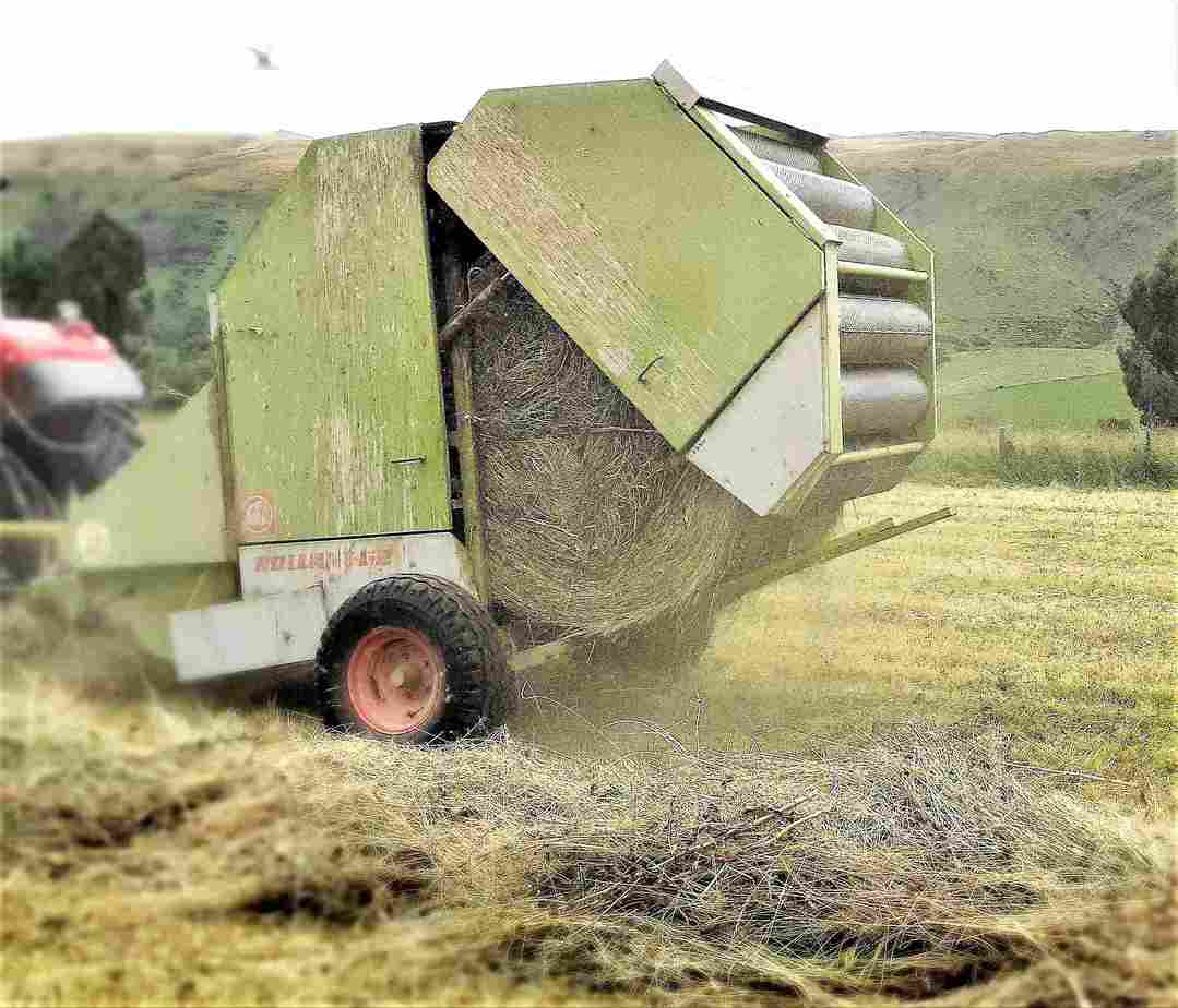 A hay baler opens to release a large round bale of hay.