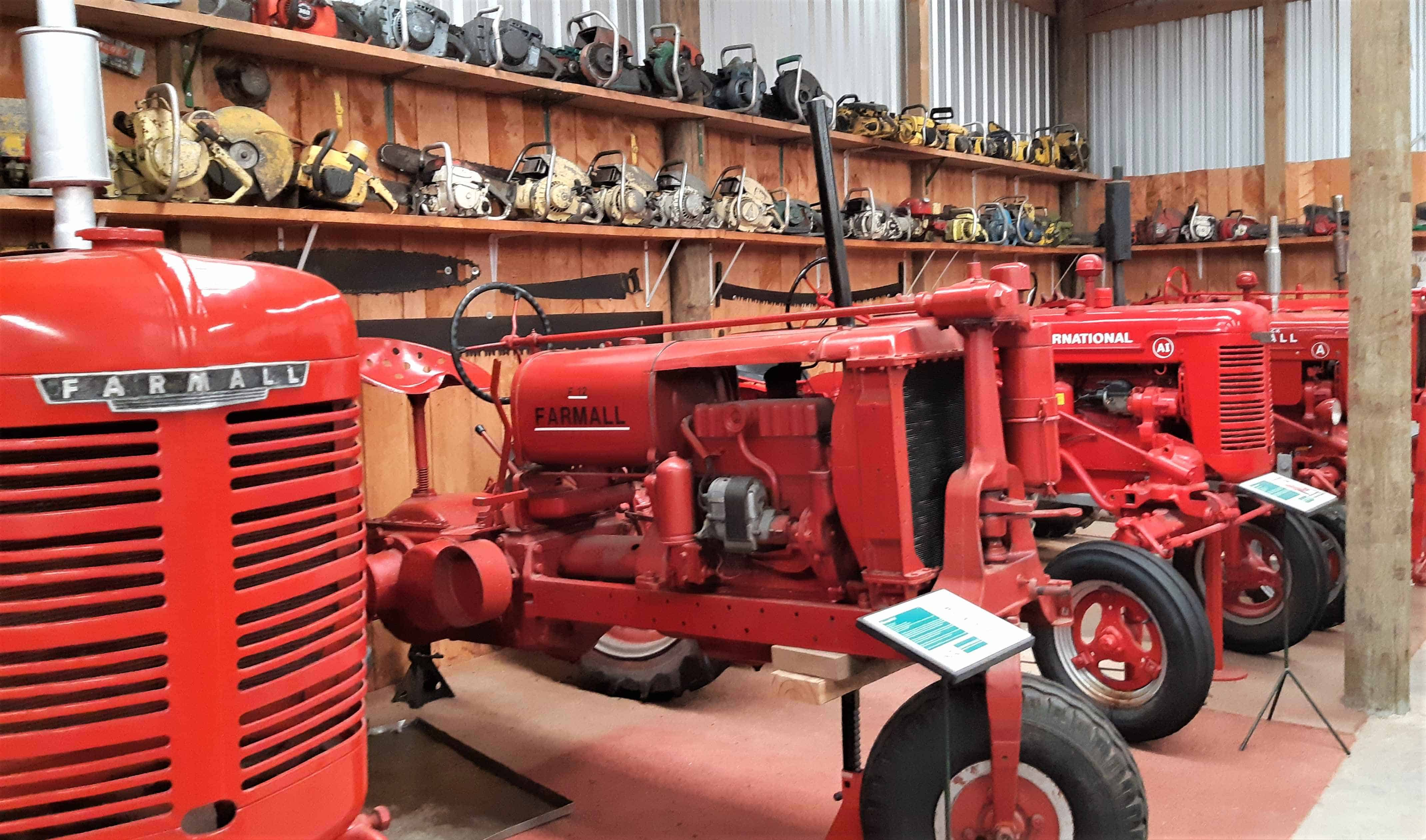 Polished red tractors lined up in the Tawhiti Museum farm hall.