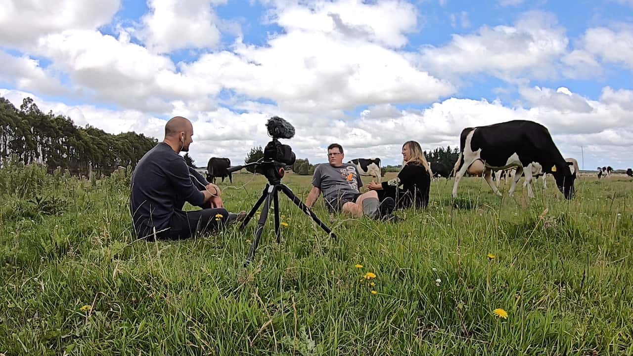 James Jubb sitting in the grass with Logan & Melissa Johnson and filming for My Southland Story.