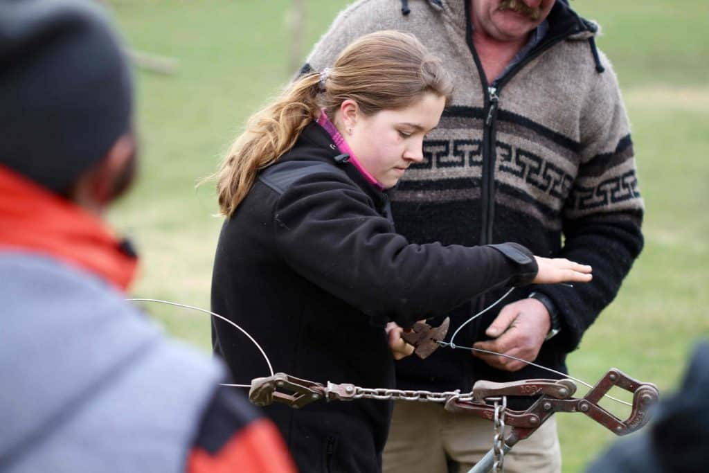 A southern girl twists some wire during the fence-fixing lesson.