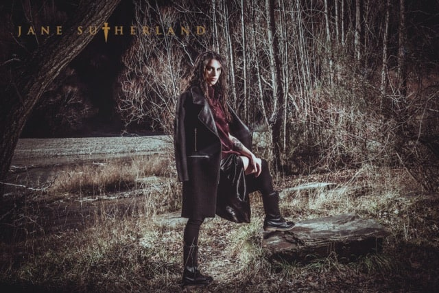 Model poses in the woods, wearing a coat by Kingston fashion designer Jane Sutherland.