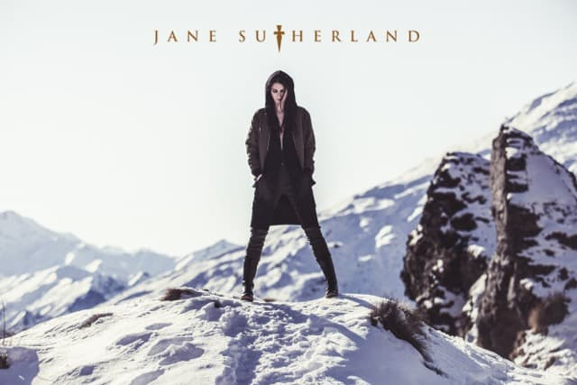 Model in mountain snow, wearing Jane Sutherland top, skirt and leggings.