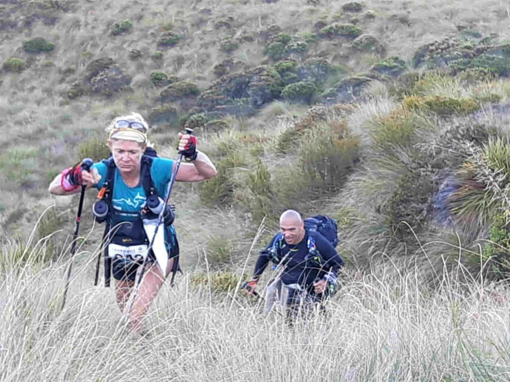 Two competitors toil up the hill through tussocks and scrub after visiting checkpoint 2.