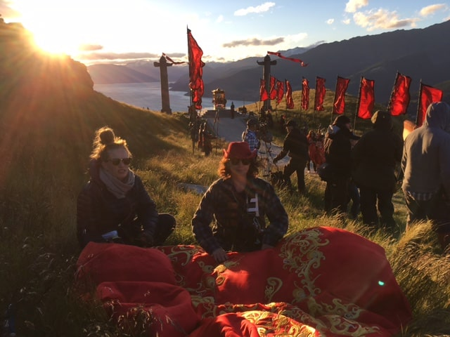 Philippa O'Brien sits on the mountainside with a huge red & gold banner, with Lake Wakatipu in the distance.
