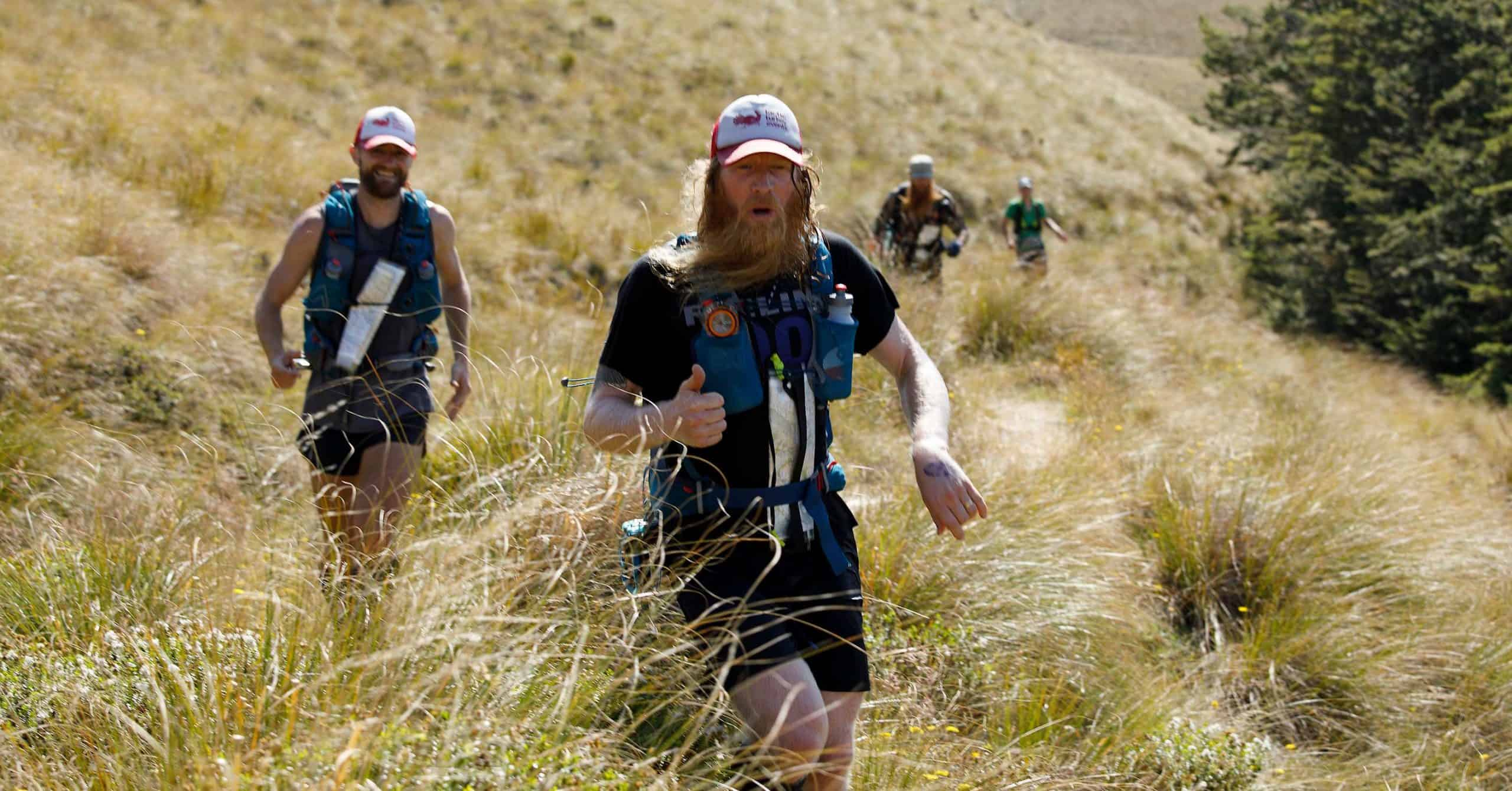 Four runners in hip-high tussocks on the Water Race trail in the Revenant Ultra Adventure Run.