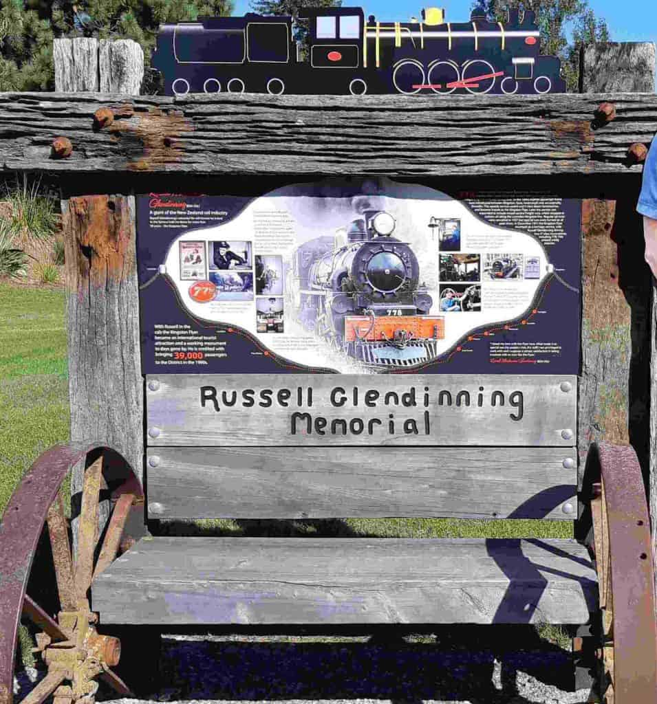 The Russell Glendinning memorial, railway sleeper & cart-wheel seat with information board. The Kingston Flyer cutout runs along the top.